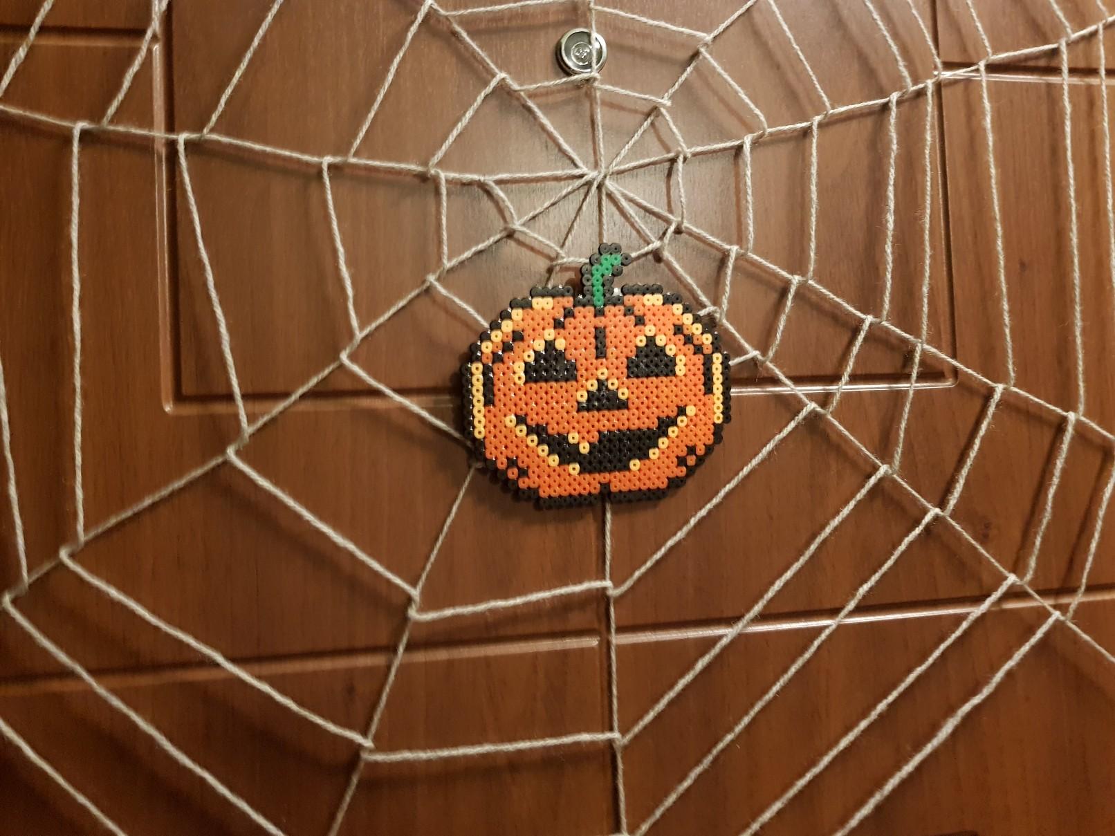 halloween spiders web on the door pumpkin